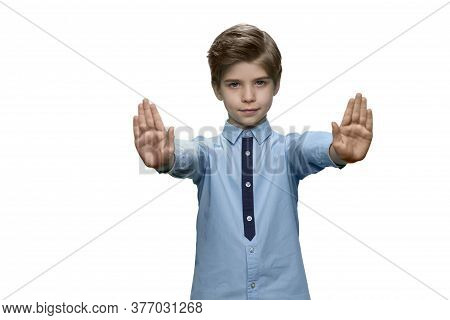 Boy In Blue T-shirt Making Stop Gesture With Both Hands On White Background. No Gesture Or Stop Sign
