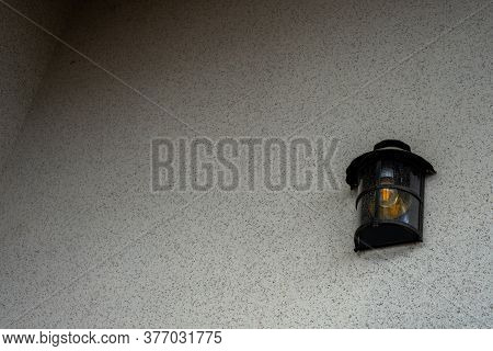 Metal Lantern In Vintage Style. Lantern On A Brown Plastered Wall. Gradient Lighting. Place For Text