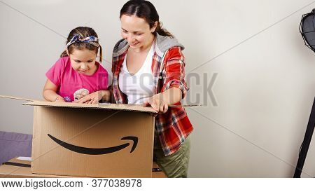 July 13, 2020 Italy, Bologna. Unpacking The Amazon Parcel. Mom And Daughter Open The Box And Joyfull