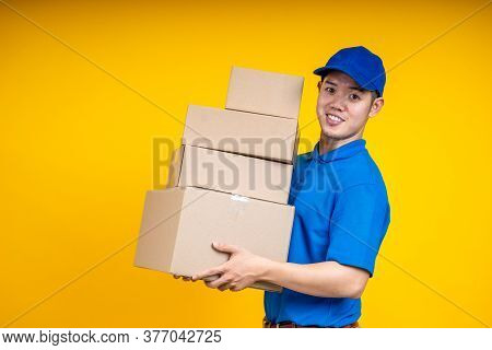Asian Delivery Man Holding Parcel Box Over Yellow Isolate Background. Work From Home And Delivery Co