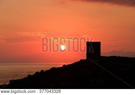 Sun Rising Behind Genoese Tower In Corsica