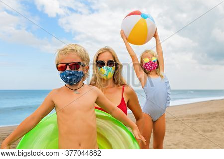 Funny Children In Sunglasses, Inflatable Toys On Tropical Sea Beach. New Rules To Wear Cloth Face Co