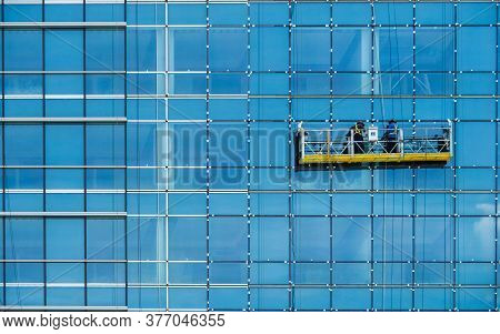 Worker Inspecting Glass Window Installation Of Tall Glass Exterior Office Building. Tall Glass Build