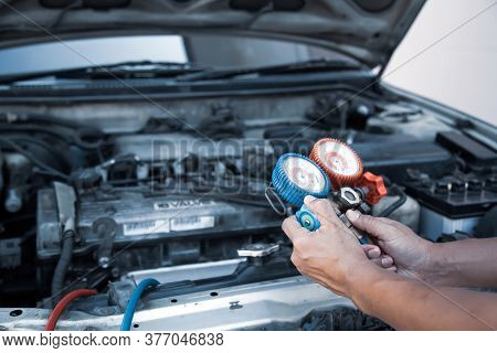 Auto Mechanic Using Measuring Equipment Tool For Filling Car Air Conditioners Fix Checking. Concepts