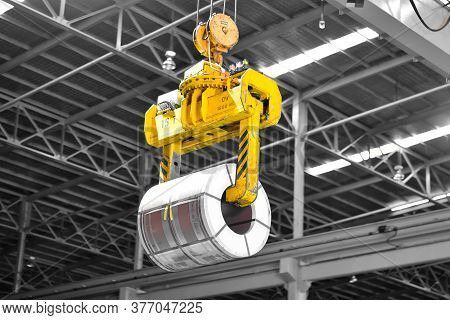 Overhead Crane Lift Up Steel Coil With Tong In Warehouse. Steel Coils Handling Equipment. Steel Ware
