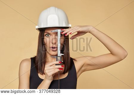 Woman In A White Protective Construction Helmet Holds A Caliper. Performs Face Measurement