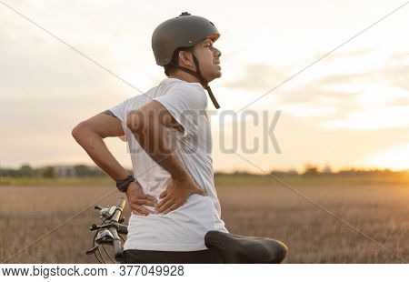 Young Asian Man Has Pain After Cycling.