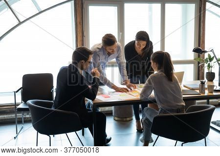 Diverse Colleagues Brainstorm Discuss Company Paperwork At Meeting