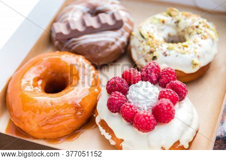 Four Pieces Of Totally Different Colorful And Delicious Looking Donuts In Ecological Carton Box. App