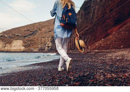 Tourist Walking On Red Beach On Aegean Sea Coastline Santorini Island, Greece. Woman With Backpack T