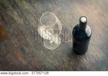 Sealed Bottle Of Red Wine And An Empty Wine Glass On The Wooden Table. Full Wine Bottle With Cork. T