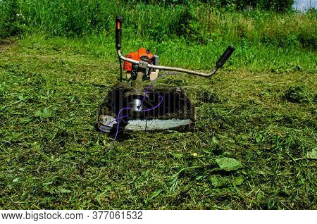 The Mowing Trimmer Lies On The Mowed Grass. Cutting Grass With A Trimer