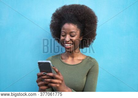 Young Afro Woman Using Mobile Smartphone - Happy African Girl Having Fun With New Trends Technology