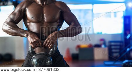 Young African Man Training Exercises Inside Gym - Fit Male Doing Kettlebell Workout Session In Sport