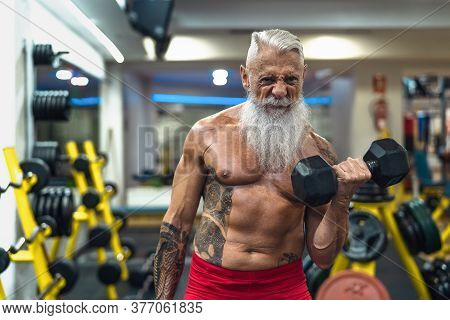 Senior Fitness Man Doing Biceps Curl Exercises Inside Gym - Fit Mature Male Training With Dumbbells