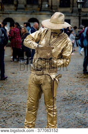 Amsterdam, Netherlands - August 8, 2018: Street Artist Dressed In Golden Clothes Pretends To Be A St