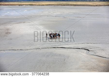 Le Mont-saint-michel, France - September 13, 2018: Group Of Hikers In The Bay At Low Tide. Hike In T
