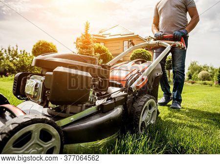 Gardener Mowing The Lawn. Landscape Design. Green Background