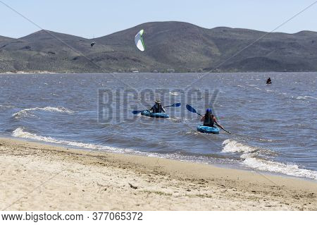 Two Kayakers  Paddling On A Windy Day Close To The Beach At Washoe Lake