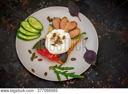 Toast With Poached Egg And Pumpkin Seeds, Smoked Pink Salmon Slices, Tomato, Arugula And Basil Leave