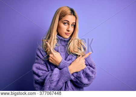 Young beautiful blonde woman wearing casual turtleneck sweater over purple background Pointing to both sides with fingers, different direction disagree