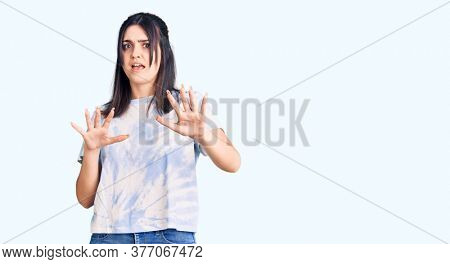 Young beautiful woman wearing casual t shirt afraid and terrified with fear expression stop gesture with hands, shouting in shock. panic concept.