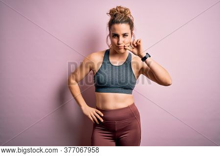 Young beautiful blonde sportswoman doing sport wearing sportswear over pink background mouth and lips shut as zip with fingers. Secret and silent, taboo talking