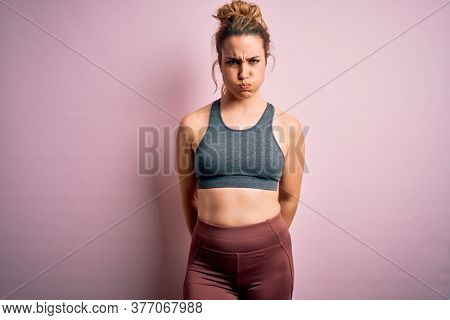 Young beautiful blonde sportswoman doing sport wearing sportswear over pink background puffing cheeks with funny face. Mouth inflated with air, crazy expression.