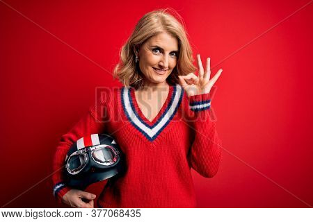 Middle age beautiful blonde motorcyclist woman holding moto helmet over red background doing ok sign with fingers, excellent symbol