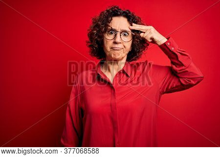 Middle age beautiful curly hair woman wearing casual shirt and glasses over red background worried and stressed about a problem with hand on forehead, nervous and anxious for crisis