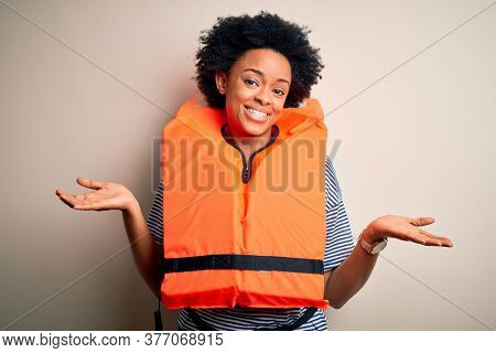 Young African American afro woman with curly hair wearing orange protection lifejacket clueless and confused expression with arms and hands raised. Doubt concept.