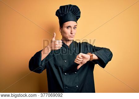 Young beautiful chef woman wearing cooker uniform and hat standing over yellow background Doing thumbs up and down, disagreement and agreement expression. Crazy conflict