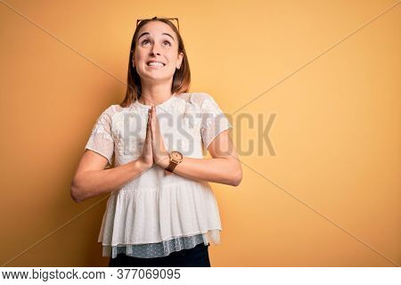 Young beautiful woman wearing casual t-shirt and sunglasses over isolated yellow background begging and praying with hands together with hope expression on face very emotional and worried. Begging.