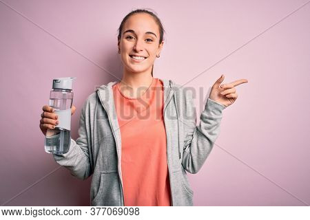 Young beautiful sporty woman doing sport drinking bottle with water to refreshment very happy pointing with hand and finger to the side