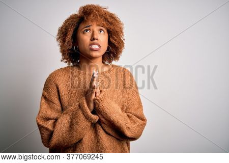 Young beautiful African American afro woman with curly hair wearing casual sweater begging and praying with hands together with hope expression on face very emotional and worried. Begging.