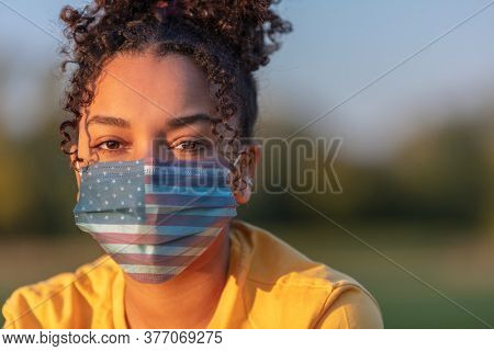Mixed race African American teenager teen girl young woman wearing a face mask decorated with the American US flag outside during the Coronavirus COVID-19 pandemic