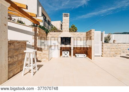 Grill Area In The Villa By The Sea. A Large Courtyard With A Stone Grill And An Open White Stone Kit