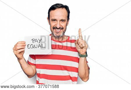 Middle age handsome man asking for social rights holding paper with pay equal message smiling with an idea or question pointing finger with happy face, number one