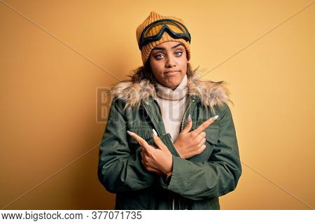 Young african american afro skier girl wearing snow sportswear and ski goggles Pointing to both sides with fingers, different direction disagree