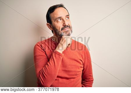 Middle age hoary man wearing casual orange sweater standing over isolated white background with hand on chin thinking about question, pensive expression. Smiling with thoughtful face. Doubt concept.
