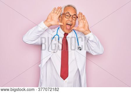Middle age senior grey-haired doctor man wearing stethoscope and professional medical coat Smiling cheerful playing peek a boo with hands showing face. Surprised and exited