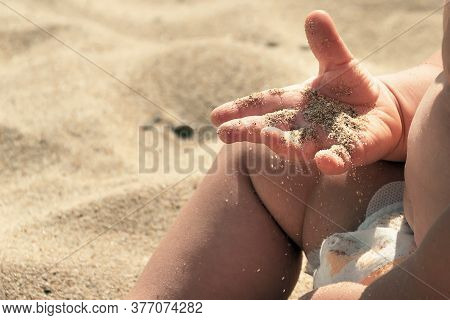 Sand In Baby Hands. Child Playing With Beach Sand. He Has For The First Time Golden Grains Of Sand I