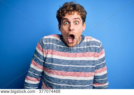 Young blond handsome man with curly hair wearing striped sweater over blue background afraid and shocked with surprise expression, fear and excited face.