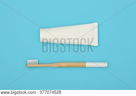 Close Up One White Toothpaste Tube And Natural Wooden Bamboo Toothbrush On Blue Background, Flat Lay