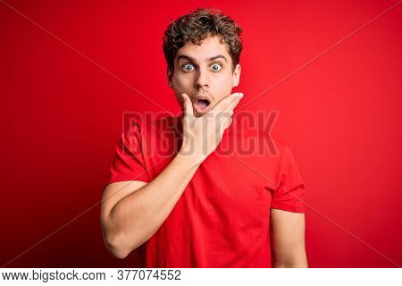 Young blond handsome man with curly hair wearing casual t-shirt over red background Looking fascinated with disbelief, surprise and amazed expression with hands on chin
