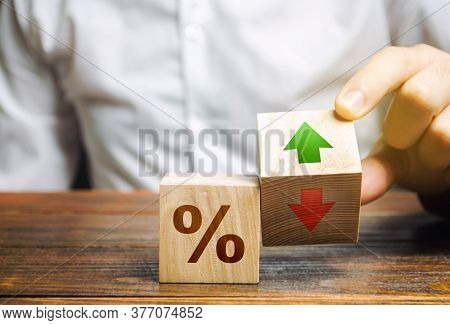 Businessman Holds Wooden Blocks With Percent And Up Or Down Arrow. Mortgage And Loan Rates. Interest
