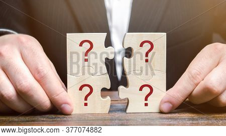 Businessman Collects Puzzles With Question Marks. Asking Questions, Searching For Truth. Riddle Myst