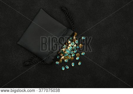 Close Up Heap Of Teal Blue Rhinestone Crystals Spilling Out Of Leather Bag Over Black Background, El