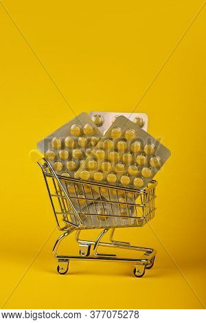 Close Up Several Different Blister Packs Of Pills In Small Shopping Cart Over Yellow Background, Con