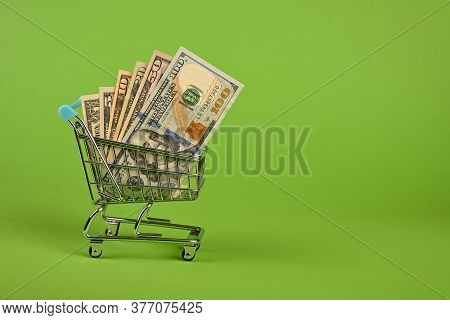 Close Up Several Different Value Us Dollar Paper Currency Banknotes In Small Shopping Cart Over Gree